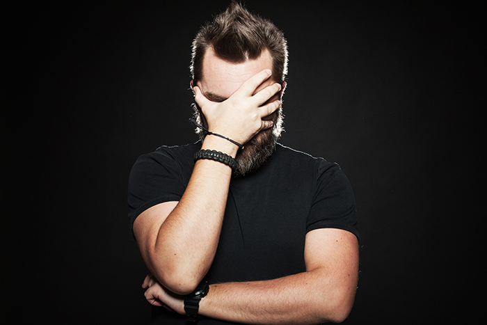 A bearded man holding his hand to his face on a black background