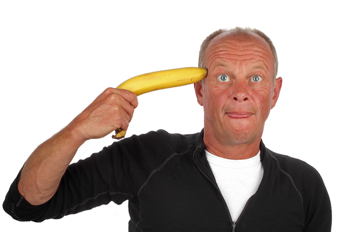 A stressed out man holding a banana to his head