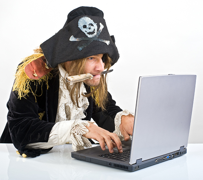 A pirate with a knife in his mouth sitting in front of a laptop