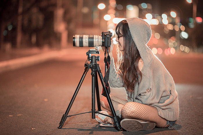 female photographer taking pictures at night
