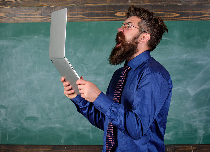A bearded man screaming at his laptop